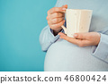 Pregnant woman holding ceramic cup of tea or coffee on belly. Young girl in blue wearing expecting 46800424