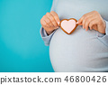 Pregnant woman holding heart-shaped cookie on tummy belly background. Young girl in blue wearing 46800426