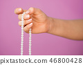 Woman, lit hand close up, counts Malas, strands of gemstones beads used for keeping count during 46800428
