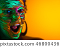 Portrait of girl with fluorescent paint makeup. Dye glowing near UV light. Woman with open mouth in 46800436