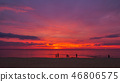 tourists on the beach in red sunset 46806575