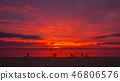 tourists on the beach in red sunset 46806576
