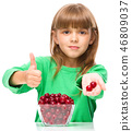 Cute girl is eating cherries showing thumb up sigh 46809037