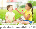 Little girl and boy are blowing soap bubbles 46809239