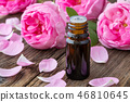 A bottle of essential oil with fresh roses 46810645