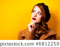 redhead woman in beret and coat on yellow 46812250