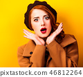 woman in beret and coat on yellow background 46812264