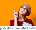 girl with notebook and pencil on yellow background. 46812654