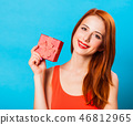 Smiling redhead woman with gift 46812965