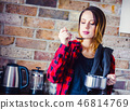 Portrait of young woman in red shirt at kitchen 46814769