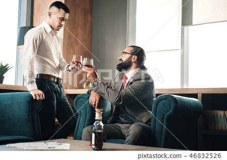 Prosperous business partners clanging their glasses drinking cognac 46832526