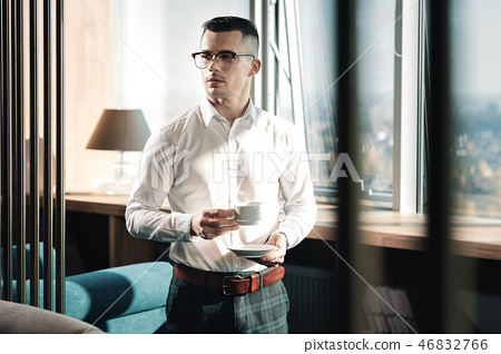 Young prosperous man standing in his office near the window 46832766
