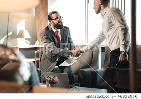 Bearded man wearing glasses standing up shaking hand of partner 46832950