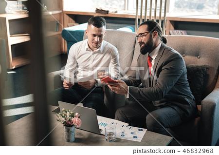 Bearded boss wearing dark grey costume talking to his trainee 46832968