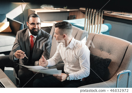 Dark-haired assistant cooperating with his bearded boss 46832972