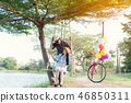 young woman on a swing, with her boyfriend. 46850311