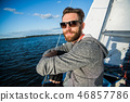 A man wearing sunglasses and casual clothes as he drives a small dinghy around a lake or river 46857786