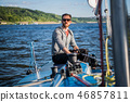 A man wearing sunglasses and casual clothes as he drives a small dinghy around a lake or river 46857811