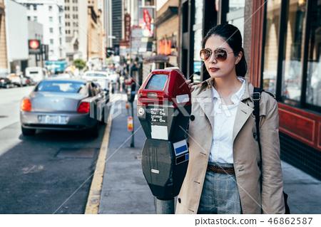 elegant office lady using parking meter on street 46862587