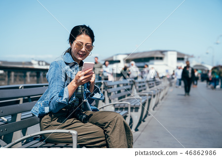 woman using mobile on bench chair 46862986