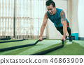 Man with battle rope exercise in fitness gym 46863909