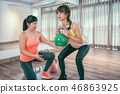 asian woman doing weight training with trainer 46863925