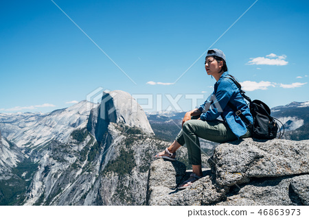 traveler sitting on the top of the mountain 46863973
