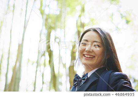 High school girl standing against bamboo forest 46864935