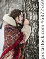 Portrait of a woman in a fur coat near a birch 46872569