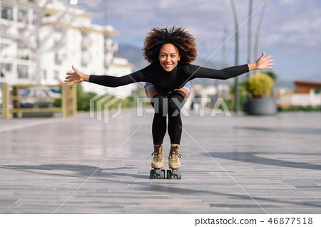 Black woman on roller skates riding outdoors on urban street 46877518