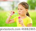 Little girl is blowing a soap bubbles 46882865