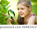 Girl is looking at tree leaves through magnifier 46883422