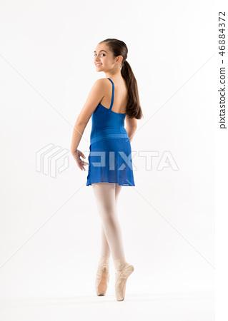 Pretty young ballerina posing on pointe 46884372