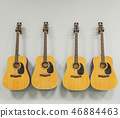 Four acoustic guitars hanging on a white wall 46884463
