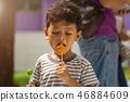 Asian boy eating a Ball plated dessert 46884609
