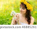 beautiful girl with dandelion flowers in green field 46885261