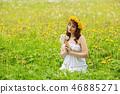 beautiful girl with dandelion flowers in green field 46885271