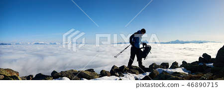 Hiker man on rocky hill on foggy valley with white clouds, snowy mountains and blue sky background. 46890715