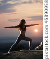 Attractive slim young woman doing yoga exercises outdoors on background of beautiful sky. 46890958