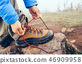 hiker tying shoelace on foggy highland mountain 46909958