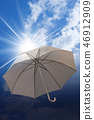 Umbrella on a blue sky with clouds and sun rays 46912909