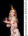 Portrait of a young funny beautiful blond girl holding birthday cake with candles on black 46924251