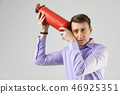 young man put a fire extinguisher to his head isolated on light background 46925351