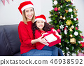 Little girl and her mother wearing santa hat  46938592