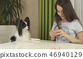 Girl teenager and dog Papillon guess on desires, girl is happy with the chosen desire 46940129