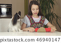 Teen girl and dog Papillon prepare cookies, rolling dough with rolling pin 46940147