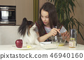 Teen girl with dog Papillon prepare cookies, knead the dough 46940160