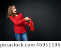 Girl holding red fire extinguisher directing at blank copy space 46951596