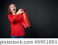 Girl holding red fire extinguisher directing at blank copy space 46951601