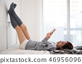 Attractive Asian Woman lying and reading a book. 46956096